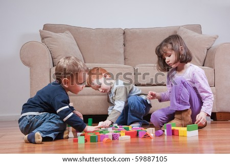 Three preschooler kids playing with blocks