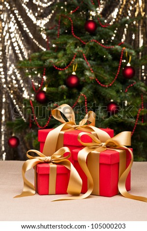 Three presents with gold ribbon, in front of a Christmas tree