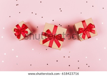 Three presents with red bow on pastel trendy pink background with little silver sparkles. Flat lay style. #618423716