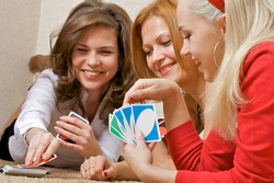 Three pretty girls lying on the floor, playing a game of cards UNO.