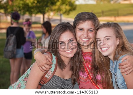 Three pretty teenage girls hugging at student campus