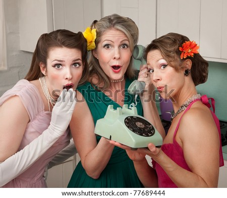 Three pretty women in kitchen with telephone