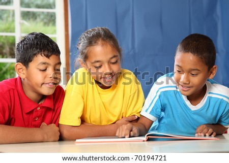 Three primary school friends reading and learning