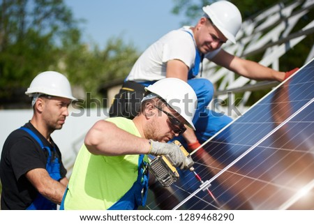 Three professional technicians installing solar photo voltaic panel to metal platform on blue sky background. Stand-alone solar system installation, efficiency and professionalism concept.