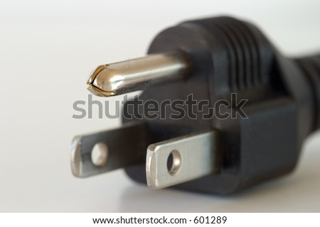 Three-pronged electrical plug with a shallow depth of field. - stock photo