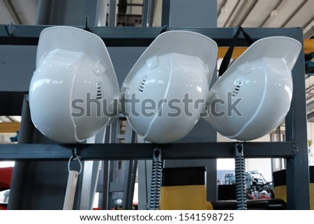 Three protective white helmets hang on the rack in the factory. Headgear of an engineer and technical specialist. The concept of safety and protective equipment.