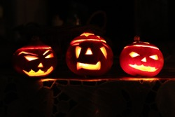 Three Pumpkins Turned into monstrous candle or jack lanterns for Halloween party