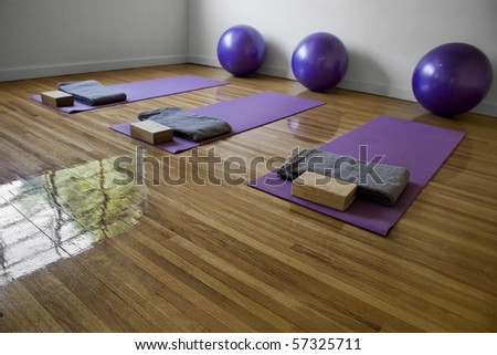 Three purple mats on a yoga classroom