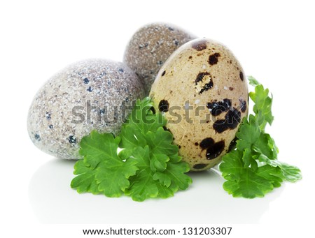 three quail eggs with parsley isolated on white background