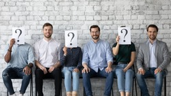 Three qualified men applicants interviewed successfully getting hired in company position concept. Six multi racial jobless people sit in line three of them hiding face behind paper with question mark
