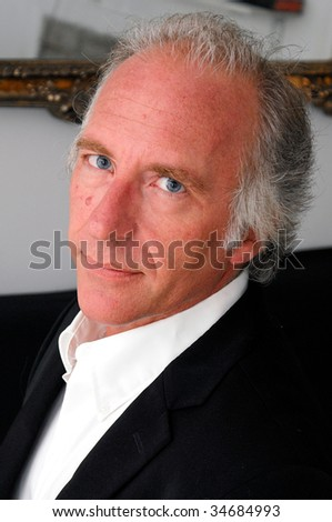 three quarter face portrait of handsome professional blue eyed older man.