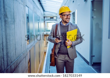 Three quarter length of handsome positive dedicated architect with folder in hands walking in building in construction process. That building is planned to be big business center. Stockfoto ©