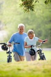 Three quarter length portrait of a happy mature couple walking with bicycles outdoors.
