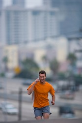 Three quarter length portrait of a young man running and talking over a mobile phone outdoors with copy space.