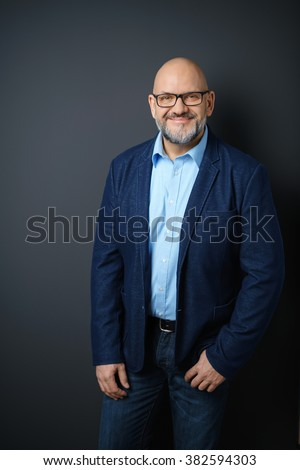 Three Quarter Length Portrait of Confident Mature Man with Facial Hair and Eyeglasses Wearing Business Casual Clothing and Standing in Studio with Dark Gray Background and Copy Space