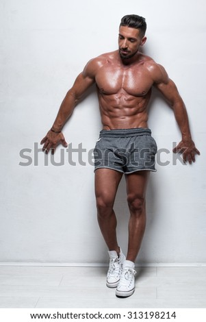 Three Quarter Length Portrait of Muscular Man Standing Shirtless with Hand on Hip Wearing Gray Athletic Shorts in Studio with White Background and Looking to the Side #313198214