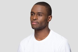 Three quarter portrait of attractive confident millennial African American man, handsome young male wearing white t-shirt, serious guy, student posing close up isolated on studio background