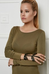 Three quarter shot of lady, wearing olive sweater with boat neckline. The young girl is looking to side, wearing leather slave bracelet with silver studs and perforated insertions in view of wings.