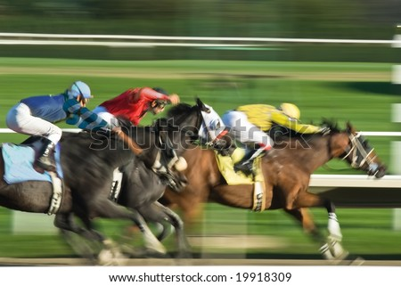 Three racing horses neck to neck in fierce competition for the finish line