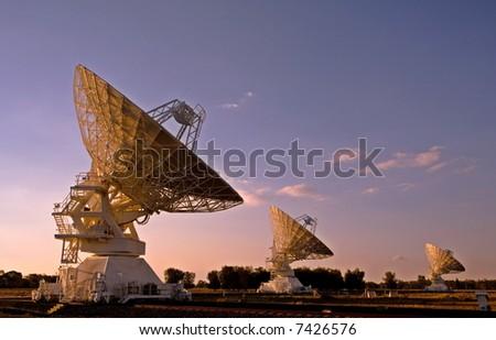 three radio telescopes photographed at sunset