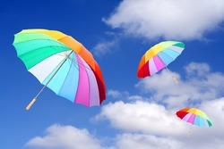Three rainbow umbrellas flying on a blue sky. Windy and rainy weather metaphor. Weather forecast theme.