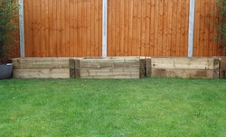 Three raised bed wooden planters or troughs for vegetables or flowers and plants (bamboo). Made from railway sleepers in domestic back garden with lawn and fence. Outdoors on a bright spring day