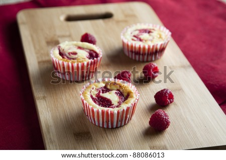 Three raspberry cheesecake muffins with fresh raspberries.