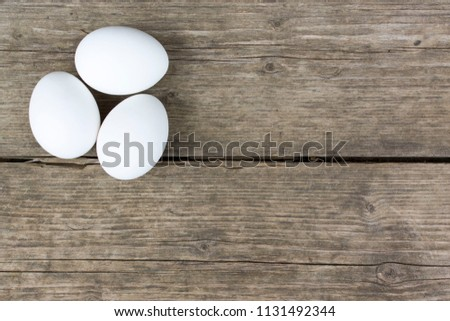 three raw white hen eggs on old ...