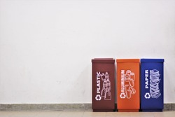 Three Recycling Bins at a corner of old white wall. Plastic, Aluminium and Paper Bin.