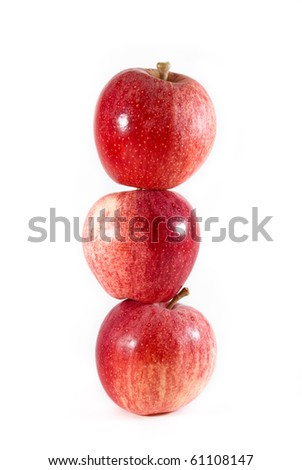 Three red and yellow gala apples balanced tall on each other on a white isolated background.