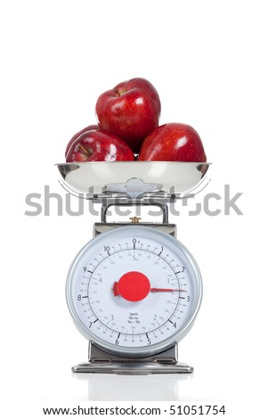 Three red apples on a food scale on a white background