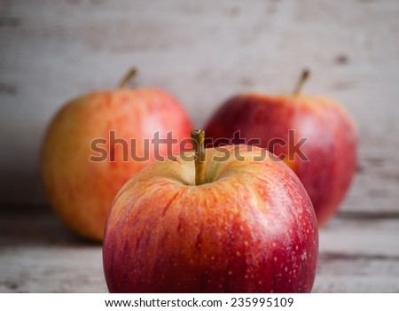 Three red apples over wooden background. One apple is in selective focus