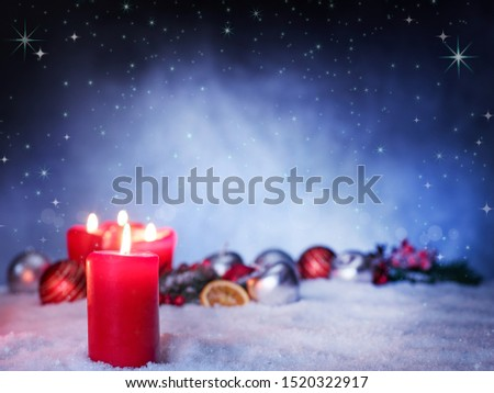 three red burning candles stand in the snow with many blurred christmas decorations in the back, like christmas balls, dried orange slices with a blue evening sky background and stars in the sky #1520322917