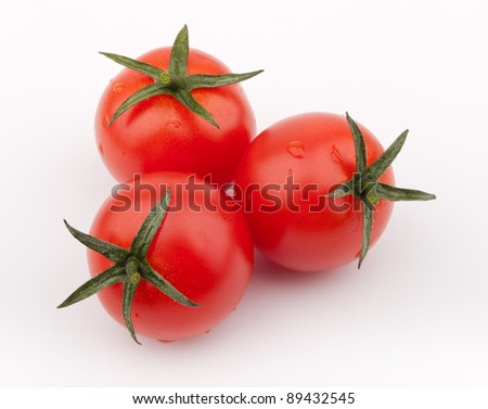 Three red cherry tomatoes, covered with some water drops.