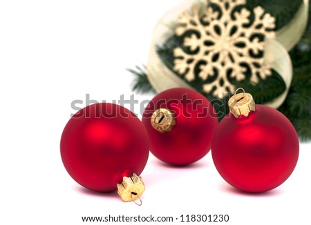 Three red christmas balls and fir, isolated on white, selective focus