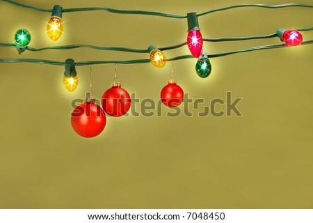 Three red christmas balls hanging on a set of colored tree lights