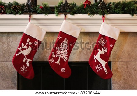 Three red christmas stockings on fireplace mantle