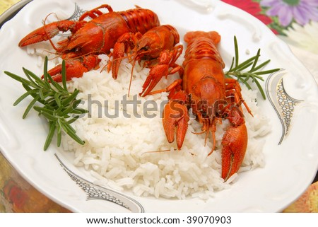 three red cooked crayfish served on plate over  rice