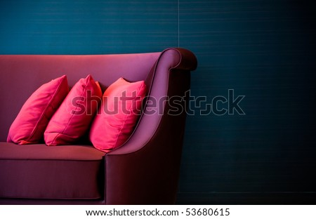Three red decorative pillows on a contemporary sofa. - stock photo