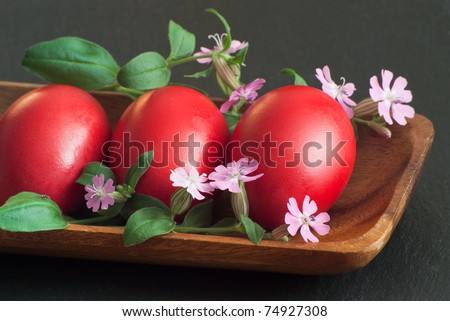 three red Easter eggs with little flowers in wood bowl