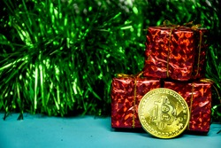 Three red gift boxes and a gold bitcoin coin are placed against the background of New Year's tinsel and against a green-blue background. Postcard with a picture of a gold bitcoin coin.