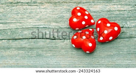 Three Red Hearts On Wooden Background. Lovely Valentines Day Decoration. Retro style toned picture