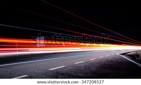 Three red lines / red light trails at night on the road