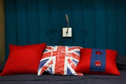 Three red pillows lie on the bed. Grey duvet. Blue wooden wall. The lamp on the wall. The design of the bedroom. Pillows in the form of an English flag.