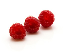 Three red raspberries isolated on white background in row
