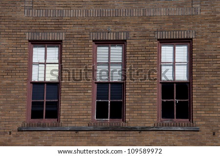 Three red rectangular windows on a large antique brick building