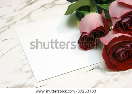 Three red roses and note on a marble table