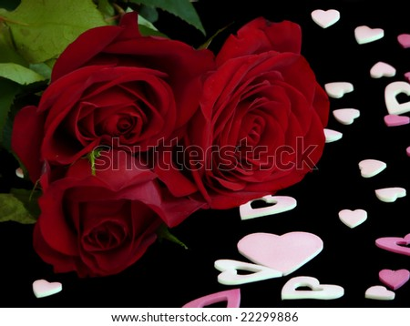 Three red roses on a black background with pink Valentine's Day hearts surrounding them.