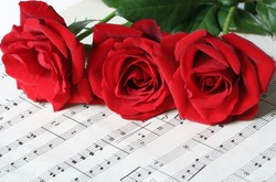 Three red roses, resting on old sheet music.
