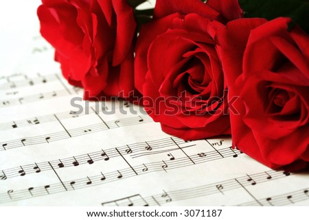 Three red roses resting on sheet music (\